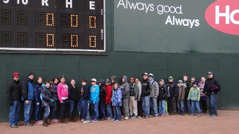 Students that completed Slugger's Reading Challenge pose for a picture in front of the Maine Monster on April 7th.