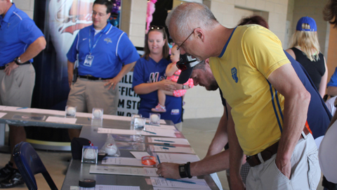 Fans mull over memorabilia Friday, May 25 during one of two in-game silent auctions held by the Drillers at ONEOK Field to raise money for Oklahoma Tornado Relief. The Drillers raised over $10,000 and donated another $10,000 to the American Red Cross.