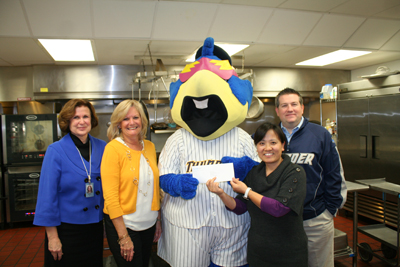 (Caption:) Paying a visit to the Trenton Area Soup Kitchen (TASK) along with Boomer, the Trenton Thunder mascot, are, from left, Patricia Hartpence, Assistant Vice President for Corporate Giving, NJM Insurance Group; Cindy Berger, NJM's Community Outreach Events Coordinator; and Will Smith, General Manager and Chief Operating Officer of the Thunder. Boomer hands NJM's donation check to Xiumei Chen, Manager of Finance and Administration for TASK.